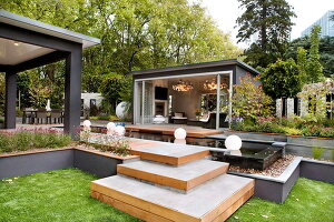 ppiger garten mit h her gelegten beeten in holzeinfassungen und einfacher sitzgarnitur auf. Black Bedroom Furniture Sets. Home Design Ideas