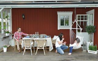weisse holzm bel mit bunten kissen und geschirr im skandinavischen stil auf einer terrasse. Black Bedroom Furniture Sets. Home Design Ideas