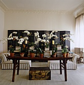 Orchids are interspersed with piles of books on the table in this living room while a large Chinese folding screen decorates the back wall