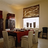 Chairs with slip covers around a table with a red tablecloth in an elegant dining room with bamboo roller blinds