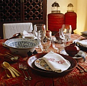 Chinese tableware with bowls and red Chinese lanterns on a table with a patterned tablecloth