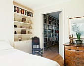 Modern bed and antiques next to open door with view of modern bookcase