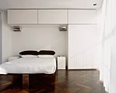 Designer bedroom with white fitted wardrobe and dark parquet floor