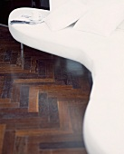 White, curved designer sofa on dark parquet flooring
