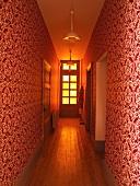 Schmaler Flur mit rot weissem Ornamentmuster auf Tapete an Wand