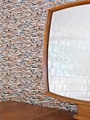 Spiegel auf Holzablage vor Wandtapete mit abstraktem Muster