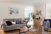 Skandinavisch maritimer Stil mit kunstvoll verarbeitetem Wurzelholz mit Glasbord im Sitzbereich eines offenen Wohnzimmers