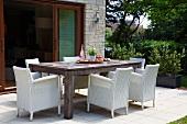 Weisse Rattansessel an großem Holztisch vor einer geöffneten Terrassentür mit Garten