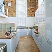 blick in eine hellblaue hochglanzk che mit hohem. Black Bedroom Furniture Sets. Home Design Ideas