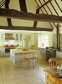 Kitchen island with bar stools in open-plan kitchen of country house with half-timbered structure