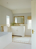 View of white-painted, wooden washstand in country-style bathroom through open door