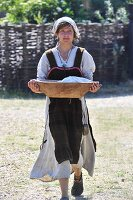 Girl in Viking costume carrying wooden bowl