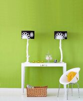 Two table lamps with black and white lampshades on table and child's chair in front of green-painted wall
