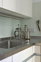 Corner of modern kitchen with stainless steel worktop