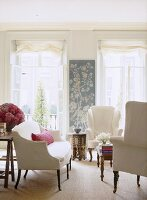 A traditional sitting room, upholstered sofa and wing back armchairs, French doors, wall hanging