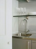 A detail of a modern kitchen, stainless steel sink unit, shelving, glassware