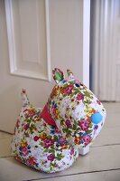 A stuffed toy made from a floral patterned material being used as a door stop