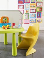 Toys and plastic eating utensils on a plastic table with child's plastic chair