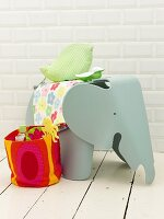 An elephant stool and a colourful fabric basket of bathing utensils