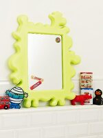 A child's mirror and toys on a shelf in the bathroom