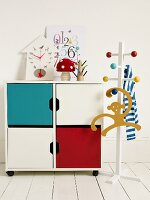 A child's clothes stand next to a colourful cupboard with a wall clock on top