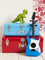 A red suitcase and a blue suitcase, a toy guitar and an stuffed animal