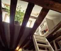 hoher altbau mit pflanzen und antiken m beln zwischen rundbogenfenstern und treppe zu bibliothek. Black Bedroom Furniture Sets. Home Design Ideas