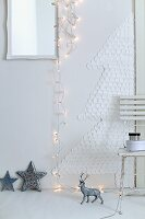 A Christmas tree made of cotton wool pads a wall with a chain of fairy lights and Christmas decorations