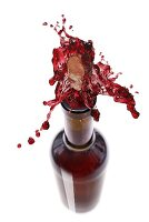 Red wine spraying out of a bottle