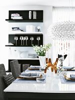 Dining table in black, white and grey with golden candlestick and crystal chandelier