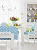 A blue and white dining room with upholstered chairs and a wooden bench with a crockery cupboard in the background