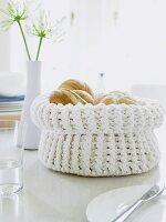 A white knitted bread basket filled with fresh rolls
