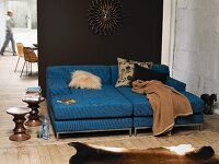 Blue sofa with scatter cushions and blanket against dark brown wall