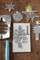 Christmas tree decorations cut out of silver paper on wooden surface