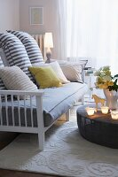 Striped scatter cushions on sofa with wooden frame