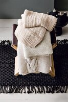 Ecru knitted blankets stacked on stool