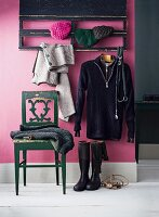 Chair below coat rack mounted on lilac wall