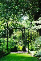 A rose arch and obelisks in a resplendent garden