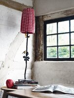 Metal lamp with red and white plaid lampshade in front of window