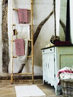 Vintage bathroom with wooden ladder as towel rack