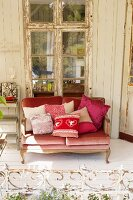 Sofa with scatter cushions on white wooden floor in front of lattice window with peeling frame