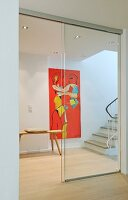 Hallway with staircase, artwork on wall and sliding glass door