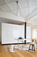 A spacious living room in a period building with a coffered ceiling and a cupboard as a room divider