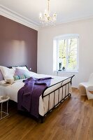 A metal bed against a purple wall in a bedroom in an apartment in a period building