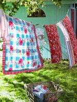 Colourful bed linen on washing line in garden