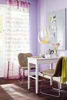 Small dining area below pendant lamp and curtain with pattern of birds in room with lilac walls