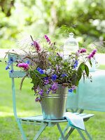 Summer flowers in metal bucket on garden chair