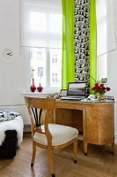 Writing desk and wooden chair in front of window with citrus green curtains