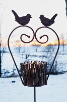 A tealight holder made from twigs on an iron stand decorated with birds