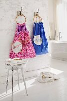 Sacks for organising laundry hanging on bathroom wall